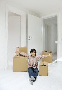 Little boy with moving boxes at new home