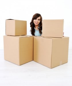 Cute young girl in a room with boxes for moving